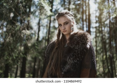 Viking woman wearing traditional warrior clothes in a deep mysterious forest