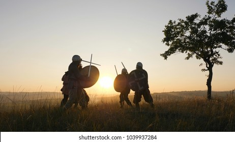 Vikings are fighting with swords and shields in the meadow. Medieval Reenactment. Contre-jour