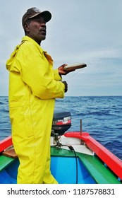 Vila do Maio ,Maio Island, Cape Verde - Jan 5 2016: local fisherman using a hand line out at open sea to fish for yellow fin tuna or wahoo in a traditional colorful dinghy
