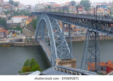 Vila Nova de Gaia, Portugal - May 30, 2020: The Dom Luis I Bridge over the Douro River and the colorful houses of Porto Ribeira, traditional facades, old multi-colored houses with red roof tiles.