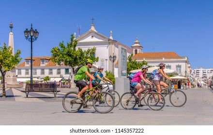 VILA REAL DE SANTO ANTONIO, PORTUGAL - July 30 2018.  A group of cyclists ride through the pretty square in the centre of the town. A popular shopping and cafe area for tourists and locals.