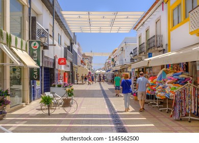 VILA REAL DE SANTO ANTONIO, PORTUGAL - July 23 2018.  Tourists and locals enjoy the shaded pedestrian shopping high street of this pretty Algarve town situated next to the Guadiana River.