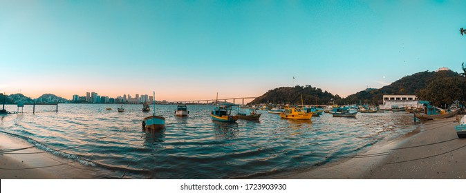 VILA VELHA, ES, BRAZIL.  05/05/2020: sunset in the Prainha neighborhood, with a view of the shore with boats and canoes, Da Penha convent, Flag of Brazil and the city of Vitoria in the background.