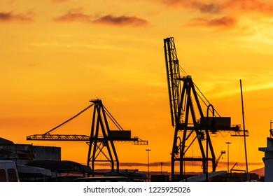 Vilagarcia de Arousa harbor crane silhouettes at golden dusk