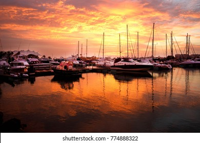 Vilamoura Marina, Algarve, Portugal at sunset, a line of boats and yaghts moored against a jetty, the sky and the water are lit bright orange by the setting sun