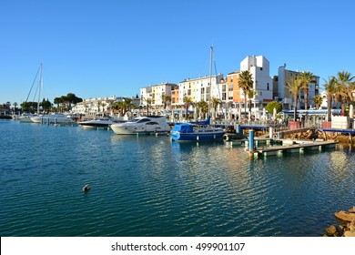 VILAMOURA, PORTUGAL - FEBRUARY 5, 2015. Harbour in Vilamoura, with boats, commercial and residential buildings, commercial properties and palms.