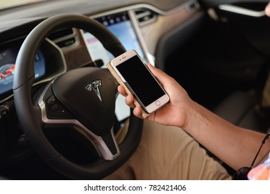Vilamoura, Portugal - June 23, 2017: The new Apple Iphone 8 and Tesla Model S on display. IT technology and automaker, energy storage, solar panel American companies based in California, USA.