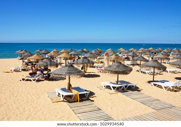 VILAMOURA, PORTUGAL - JUNE 6, 2017 - Tourists sunbathing on the beach with views over the Atlantic Ocean, Vilamoura, Algarve, Portugal, Europe, June 6, 2017.