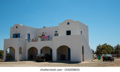 Vilchada, Greece - July 18 2019:   A whitewashed house with arched roof, balcony and cars parked outside on the Perissa to Vilchada road