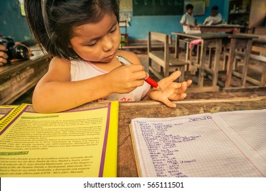 Villa Alcira, Bolivia -circa June 2009: Young girl writes with pen on her hand at school at Villa Alcira, Bolivia. Documentary editorial.
