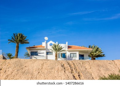villa apartment residence in desert nature scenic environment with palm trees garden on blue sky background, outdoor picturesque colorful photography