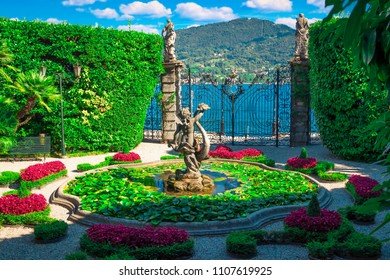 VILLA CARLOTTA, ITALY - AUGUST 02, 2015: Old fountain with stone statue in beautiful garden, villa Carlotta, Como lake, Italy.