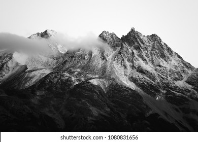 Villa Cerro Castillo, Región de Aysén / Chile - 03 17 2018: Black and white mountain range in Patagonia with some clouds just slightly touching it.