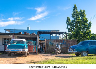 Villa Clara, Cuba- September 9, 2018: A private car body shop on a rural area. There are two vintage obsolete cars waiting outside.