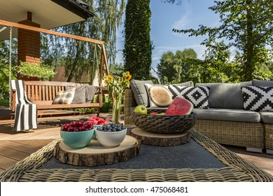 Villa patio with rattan coffee table, large sofa and wooden garden swing