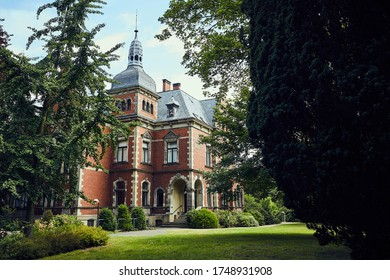 Villa Schloss in Germany an old brick building in a park / garden in summer with a blue sky, in the foreground are trees, the villa has a tower, you can see the entrance