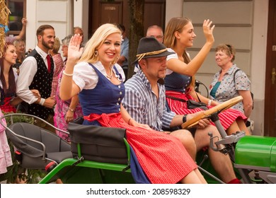 VILLACH, AUSTRIA - AUGUST 2: Participants riding a tractor at the procession of 'Villacher Kirchtag', the largest traditional folk festival in Austria, August 2, 2014 in Villach, Austria.