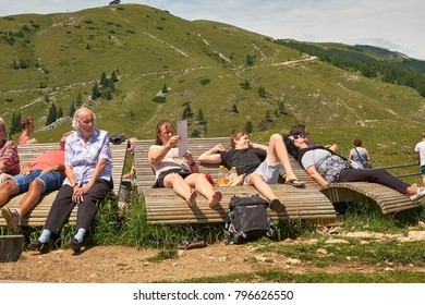 VILLACH, AUSTRIA - JULY 29, 2017: Tourists relaxing in the sun on the soft wood benches at the bottom of the hiking pathways to the top of Mount Dobratsch