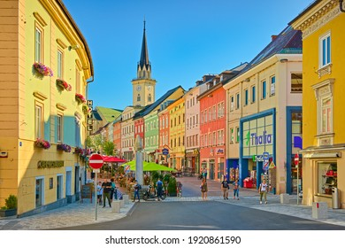 Villach - July 2020, Austria: View of the main street with colorful historical houses and the main square in a small Austrian city. People are walking along the street with shops, bars, and restaurant