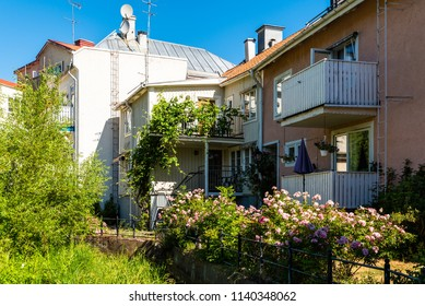 Village back yard with flowers and other vegetation along a fence and on balconies. Location Gamleby in Smaland, Sweden. Logos removed.