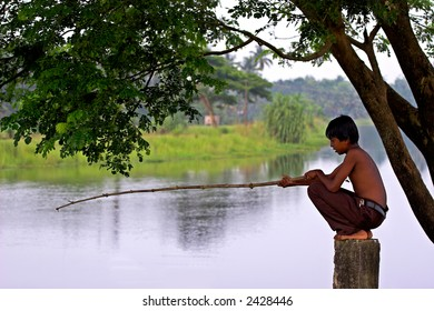 A Village boy fishing patiently on river bank