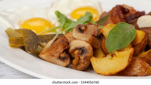 Village breakfast - fried eggs with fried potatoes, greaves, mushrooms, pickled cucumbers and croutons of brown bread.