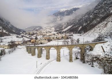 Village of Brusio in the Swiss Alps (Valposchiavo) - Viaduct of Brusio and red train of Bernina