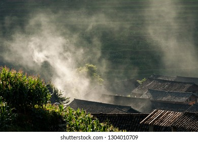 Village building rooftops and smoke in rice terraces landscape China