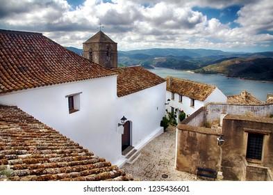 Village of Castellar de la Frontera, typical street with flowers in the white facades, in Cadiz.