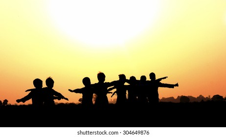Village children returning home happily from fields during sunset in India