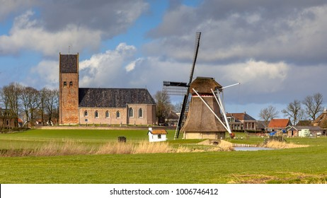Village with church and historic windmill on Frisian countryside. Just North of Leeuwarden, Friesland