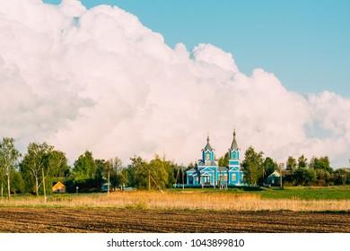 A village church made of wood on a background of cumulus huge clouds. Krasnyy Partizan, Dobrush District, Gomel Region, Belarus.