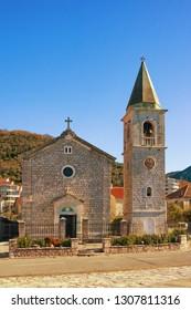 Village church in Mediterranean. Montenegro, Tivat. View of Catholic Church of Saint Roch in Donja Lastva village on sunny winter day