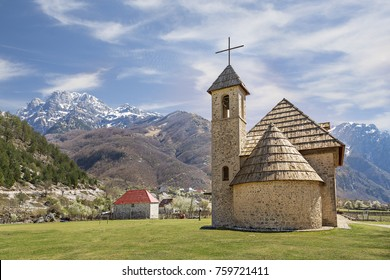 Village church in the Theth Valley with snow capped mountains in the background, in Albania.
