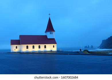 The village church of Vik on top of a small hill, with misty sea in the early morning as background, Vik, Iceland