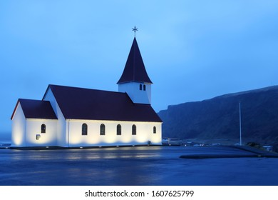 Village church of Vik in South Coast of Iceland, surrounded by mountains and sea, in a misty early morning during winter