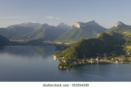 Village of Duingt with the castle at the southern Lake Annecy with surrounding rock faces and green forests of the Savoie mountains after sunrise in warm light