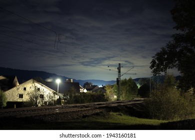 A village during nighttime with traintracks in the front