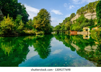 Village Fontaine-de-Vaucluse, Provence, France. The Sorgue river in summer. Colorful landscape in green.