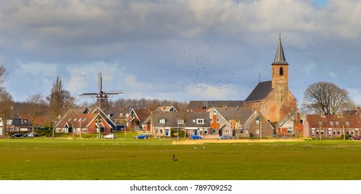 Village in Friesland with church and historic windmill on Frisian countryside. Just North of Leeuwarden, Friesland.