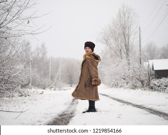 A village girl in a large sheepskin coat on a snowy rural road. Portrait of child