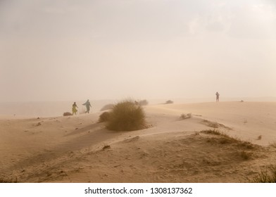 Village girls are running towards safe place to escape from the sand storm in the Thar desert