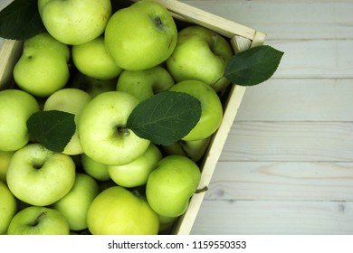 Village green of fresh ripe apples in box on white wooden table