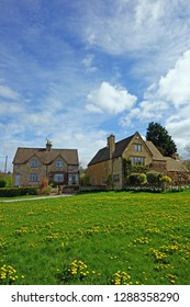 The village green full of dandylions in the Cotswold village of Wyck Rissington with a blue sky but cloudy spring sky, The Cotswolds, Gloucestershire, UK