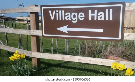 Village Hall direction sign fixed to roadside fencing in rural south northamptonshire with daffodils in foreground during early spring sunshine