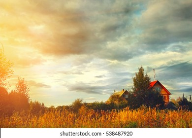 village house on field and cloudy sky autumn background.
