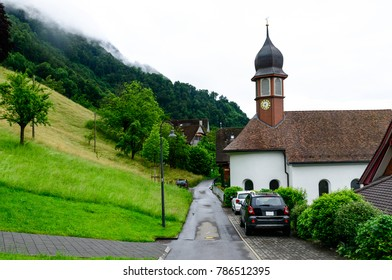 Village Kehrsiten, Switzerland on bank of lake Luzern with a quiet street passing by the clock tower and cars parked alongside.