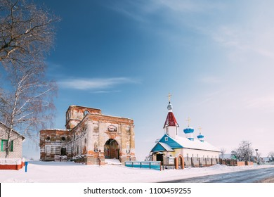Village Lenino, Dobrush District, Gomel Region, Belarus. Old Ruined Orthodox Church Of The St. Nicholas Near New Church In Winter Day. Historical Heritage.