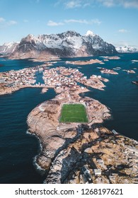 Henningsvær is a village in the Lofoten Islands hosting about 500 people. The peculiarity of this place is its soccer field with synthetic grass surrounded by the sea water.