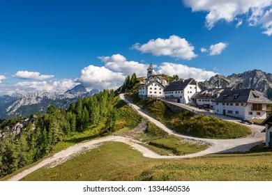 Village of Monte Santo di Lussari (1790 m) and the peak of Mangart (2677 m.) in the Julian Alps. Tarvisio, Friuli Venezia Giulia, Italy, Europe